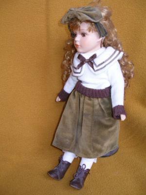 Bábika- v hnedo-zelenej sukni s veľkou mašlou vo vlasoch
