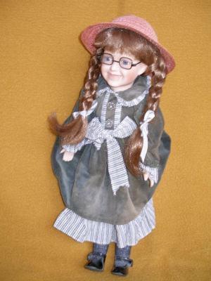 Bábika - blondínka s vrkočmi, okuliarmi a klobúkom